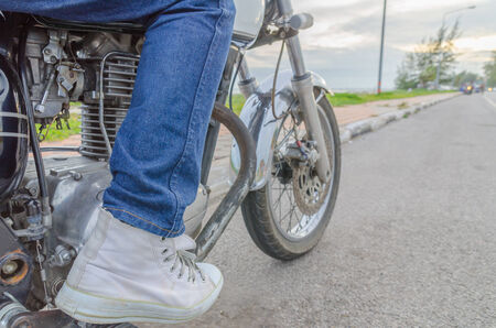 singly: Someone bestride old motorcycle parking on the roadside in evening Stock Photo