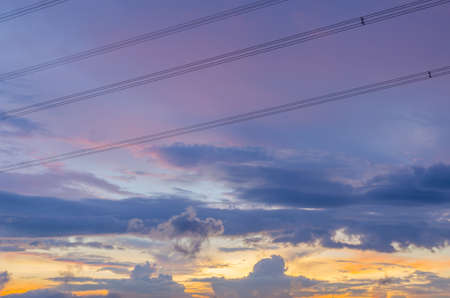 High voltage power lines cross on colorful cloud photo