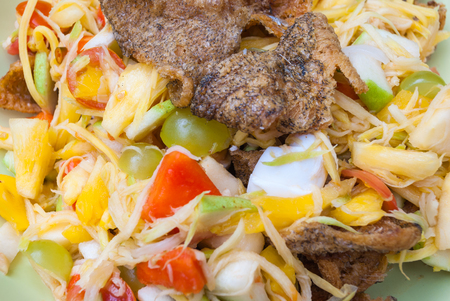 Closeup to Fruit Salad with Salted Egg and Crispy Fried Fish Background
