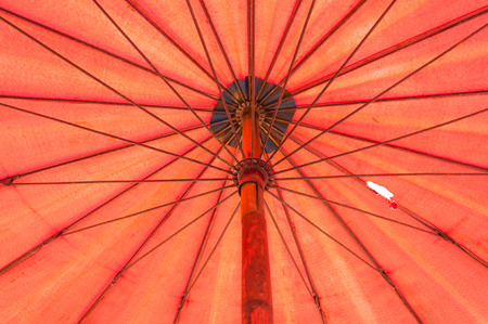 Closeup to Under Bamboo Orange Red Umbrella Фото со стока