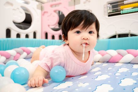 Asian Thai Baby Girl Vomit on Bed after Drink Milk Stock Photo