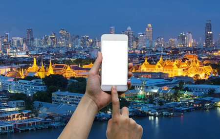 asian art: Hands touching smartphone in front of temple of emerald buddha, grand palace at night in Bangkok, Thailand