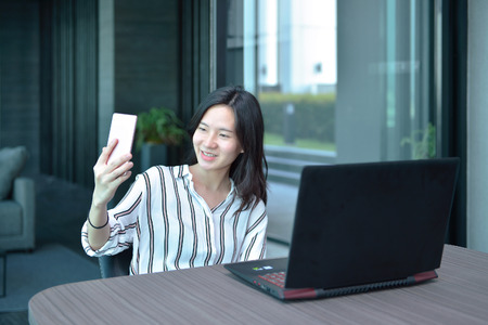 lady on phone: Casual Business Asian Woman taking a selfie with smartphone in front of a laptop in condo Stock Photo