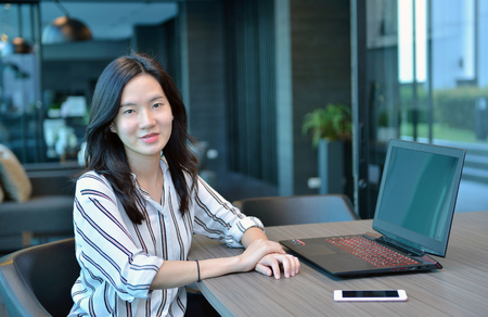 lady on phone: Casual Business Asian Woman smiling in front of a laptop in condo Stock Photo