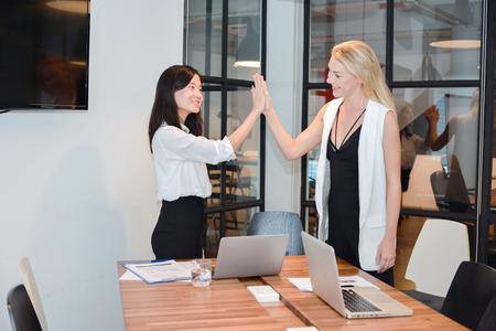 Group of business people meeting in a meeting room, high fives 版權商用圖片