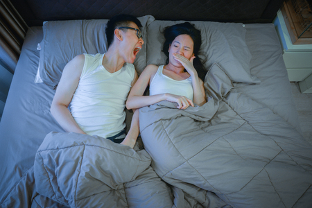 Asian couple with bad breath issues on bed at night