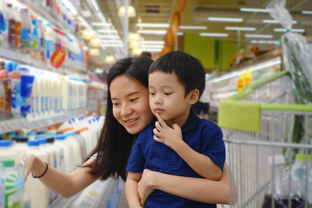 Young Asian mother and her kid shopping in supermarket with blurry background
