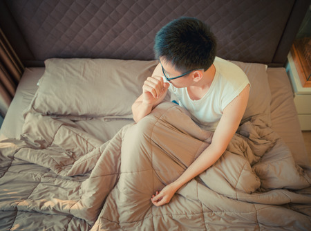 Asian man suffering from depression on bed