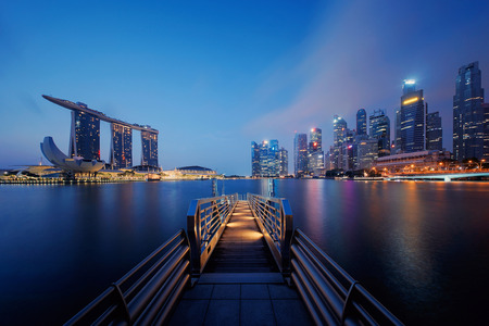 Pier in Downtown Singapore city in Marina Bay area. Financial district and skyscraper buildings at night.