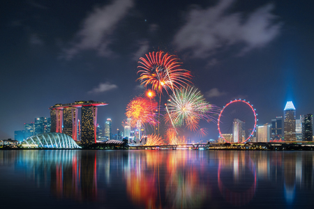 Fireworks of Singapore National Day in Downtown Singapore city in Marina Bay area at night. Financial district, The Ferris Wheel, and skyscraper buildings.