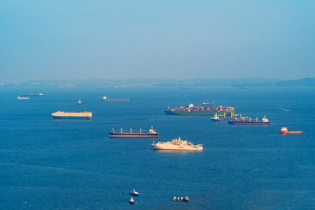 Cargo tanker ships in transportation concept. Shipping boats at Singapore harbor with blue sky at noon. Clear blue sea.