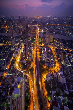 Aerial view of cars on Taksin Bridge in financial district and skyscraper buildings in transportation concept. Top view of urban city at night, Sathorn road, Bangkok. Downtown area, Thailand. 스톡 콘텐츠