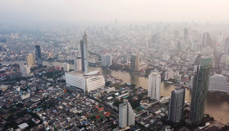 Aerial view of curve of Chao Phraya River and Taksin Bridge in financial district and skyscraper buildings. Urban city, Bangkok. Downtown area at sunset, Thailand.