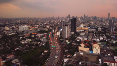 Cars driving on roads and BTS skytrain. Highways in Bangkok City at sunset in transportation concept. Aerial view of Financial district and skyscraper buildings. Downtown area at sunset, Thailand. Stock Photo