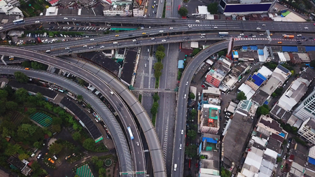 Cars driving on bridge roads shaped curve highways with skyscraper buildings. Aerial view of Expressway Bangna, Klong Toey in structure of architecture concept, Urban city, Bangkok, Thailand.