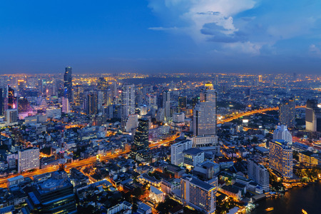 Aerial view of Sathorn, Bangkok Downtown. Financial district and business centers in smart urban city in Asia. Skyscraper and high-rise buildings at night.