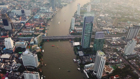 Aerial view of Chao Phraya River, Bangkok Downtown. Financial district and business centers in smart urban city in Asia. Skyscraper and high-rise buildings at sunset.