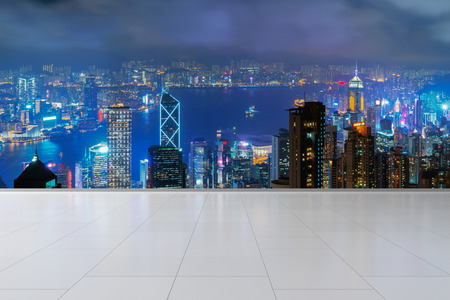 Hong Kong City and Victoria Harbour with tiles flooring. Financial district in downtown and business centers in smart urban city in Asia. Skyscraper and high-rise buildings at night.