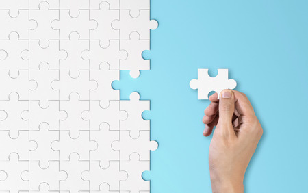 Hand putting a piece of white jigsaw puzzle. Pattern texture separated in strategy and solution of team business success partnership concept on blue background.
