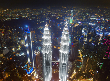 Top of Petronas Twin Towers. Aerial view of Kuala Lumpur Downtown, Malaysia. Financial district and business centers in smart urban city in Asia. Skyscraper and high-rise buildings at night. Editorial
