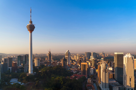 Menara Kuala Lumpur Tower with sunset sky. Aerial view of Kuala Lumpur Downtown, Malaysia. Financial district and business centers in urban city in Asia. Skyscraper and high-rise buildings at noon.