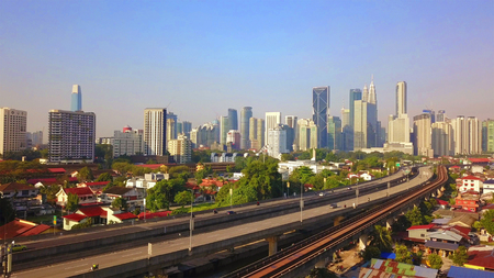 Aerial view of Kuala Lumpur Downtown, Malaysia and highways road. Financial district and business centers in smart urban city in Asia. Skyscraper and high-rise buildings at noon with blue sky. Banque d'images