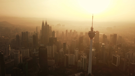 Menara Kuala Lumpur Tower with the sun. Aerial view of Kuala Lumpur Downtown, Malaysia. Financial district and business centers in urban city in Asia. Skyscraper and high-rise buildings at sunset.