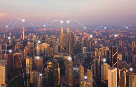 Digital network connection lines of Kuala Lumpur Downtown, Malaysia. Financial district and business centers in smart city in technology concept. Skyscraper and high-rise buildings at sunset