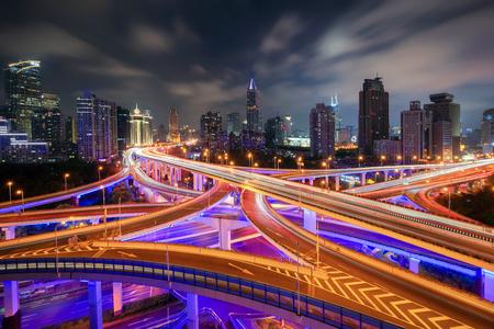 Luchtfoto van snelwegen in Shanghai Downtown, China. Financiële wijk en zakencentra in slimme stad in Azië. Bovenaanzicht van wolkenkrabber en hoogbouw 's nachts. Stockfoto