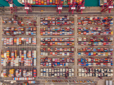 Aerial top view of container cargo ship in the export and import business and logistics international goods in urban city. Shipping to the harbor by crane in Victoria Harbour, Hong Kong.