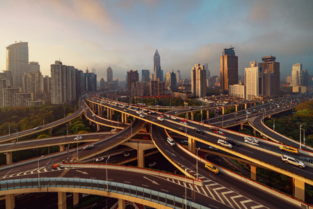 Aerial view of highways in Shanghai Downtown, China. Financial district and business centers in smart city in Asia. Top view of skyscraper and high-rise buildings at sunset. Imagens