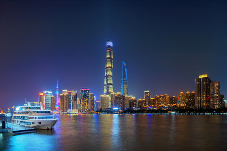 Shanghai Downtown with a boat and Huangpu River, China. Financial district and business centers in smart city in Asia. Top view of skyscraper and high-rise buildings at night. Stock Photo