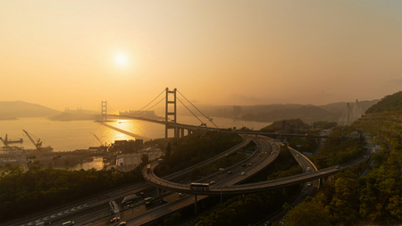 Aerial view of Tsing Ma Bridge. Highways in Hong kong with structure of suspension architecture in transportation and travel concept. Urban city at sunset.