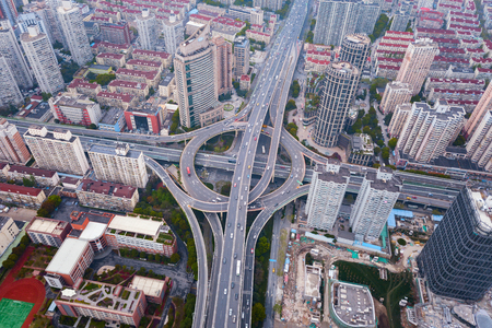 Aerial view of highway junctions with roundabout. Bridge roads shape circle in structure of architecture and transportation concept. Top view. Urban city, Shanghai, China. Stock Photo