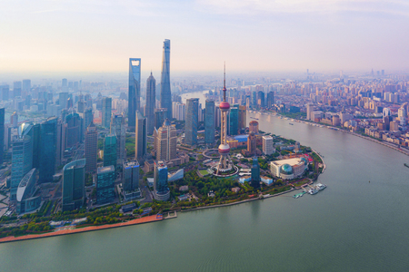 Aerial view of skyscraper and high-rise office buildings in Shanghai Downtown with Huangpu River, China. Financial district and business centers in smart city in Asia at sunrise.