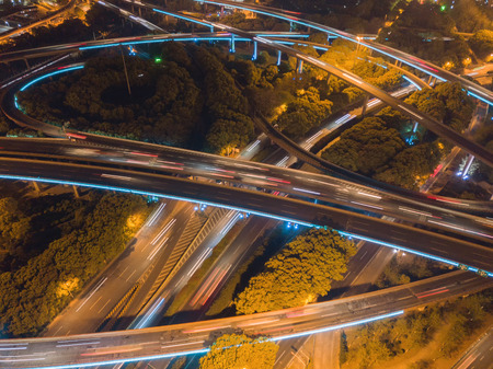 Aerial view of highway junctions at night. Bridges, roads, or streets in connection or transportation concept. Structure of architecture in urban city, Shanghai Downtown, China.