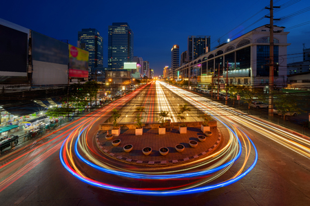 Car lights with U turn road in Sutthisan district with architecture buildings in transportation concept. Urban city, Bangkok at night, Thailand. Stock Photo
