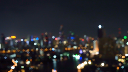 Bokeh background of skyscraper buildings in city with lights, Blurry photo at night time. Cityscape Imagens