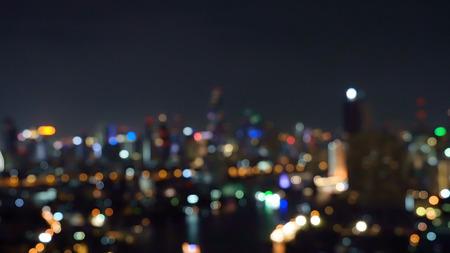 Bokeh tło budynków drapaczy chmur w mieście ze światłami, rozmazane zdjęcie w nocy. Pejzaż miejski Zdjęcie Seryjne