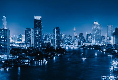 Luchtfoto van boten en Taksin Bridge met Chao Phraya River, Bangkok Downtown. Thailand. Financiële wijk en zakencentra in slimme stedelijke stad. Wolkenkrabber en hoogbouw 's nachts. Stockfoto