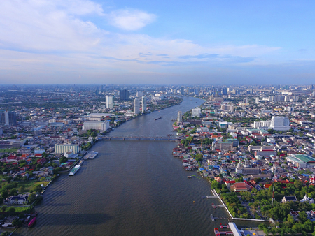 Aerial view of buildings with Chao Phraya River in transportation concept. Bangkok skyline background, Urban city in downtown area at sunset, Thailand.