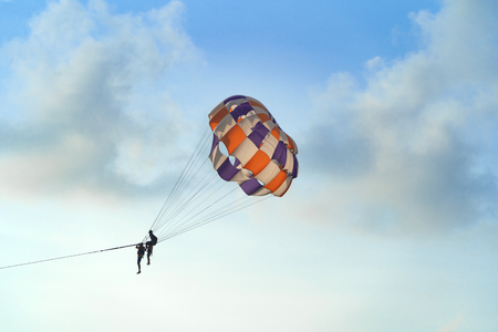 People flying in a colorful parachute or parasail together with blue sky and clouds in freedom and travel concept.