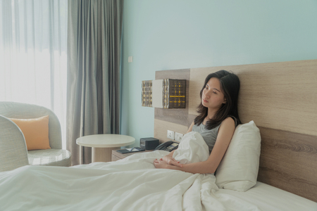Asian woman thinking about problems and suffering from depression on bed in a modern bedroom with white blanket. Banco de Imagens - 124874591