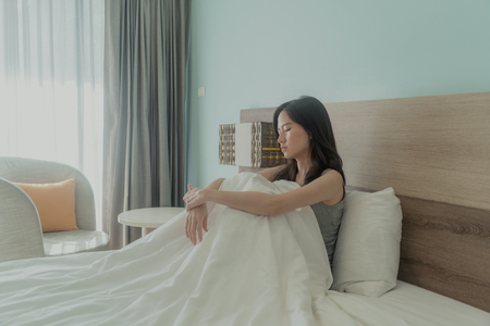 Asian woman thinking about problems and suffering from depression on bed in a modern bedroom with white blanket.