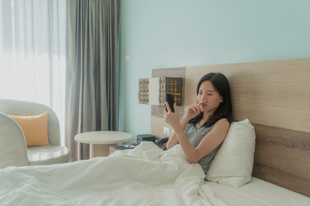 Asian woman using a mobile phone, thinking about problems and suffering from depression on bed in a modern bedroom with white blanket. Banco de Imagens