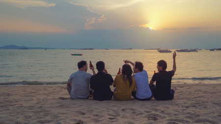Group of Thai people, Asian friends, clanging bottles of beer together and celebrating on holiday in party at the beach or sea in summer at sunset time Фото со стока