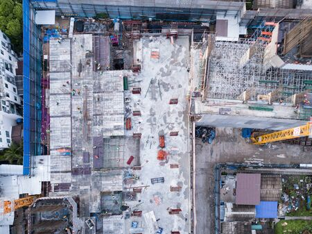 Aerial view of busy industrial construction site workers with cranes working. Top view of development high rise architecture building at noon. Banco de Imagens - 124874982