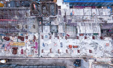 Aerial view of busy industrial construction site workers with cranes working. Top view of development high rise architecture building at noon.