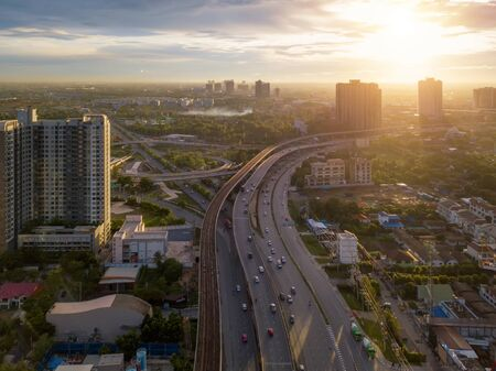 Aerial view of cars driving on highway junctions. Bridge roads in structure of architecture and transportation concept. Top view. Urban city, Bangkok at sunset, Thailand.
