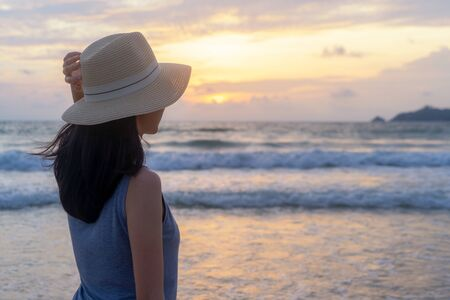 Happy Asian woman relaxing and enjoying at the beach during travel holidays vacation outdoors at ocean or nature sea at sunset time, Phuket, Thailand